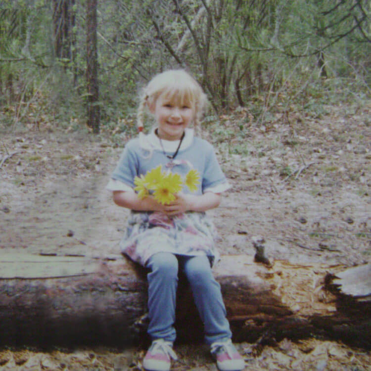 Caitey in the woods as a kid