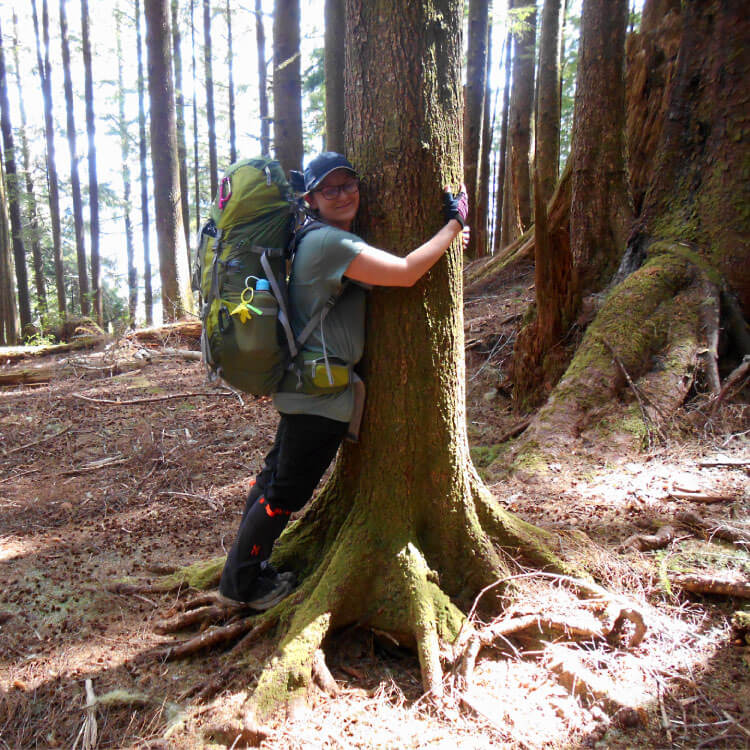 Caitey hugging a tree on the West Coast Trail